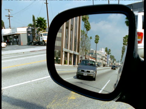 view in wing mirror as cars approach and pass parked car, california - moving past stock videos & royalty-free footage