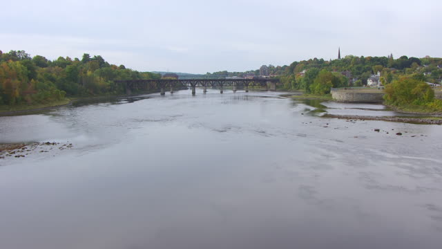 ws aerial pov view kennebec river with bridge in background/ augusta, maine, united states - kennebec river stock videos & royalty-free footage