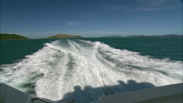 view looking back at wake created from stern of cruiser boat - coastline in distance on horizon / close up whitewash of wake water wave - wake water stock videos & royalty-free footage