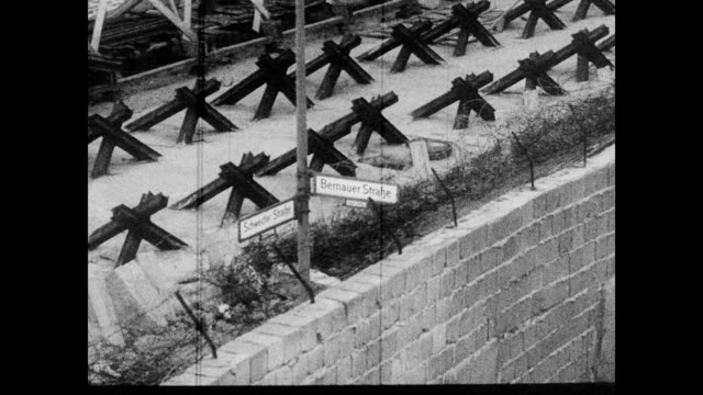 vidéos et rushes de / view looking from berlin wall onto busy city streets below / tram car traveling down the road / street signs along the wall / bricked up buildings... - 1962
