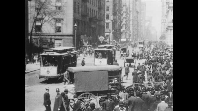 view looking north on broadway at the intersection of wall street in front of trinity church / crowded sidewalk on broadway / horsedrawn streetcar... - cocchio video stock e b–roll