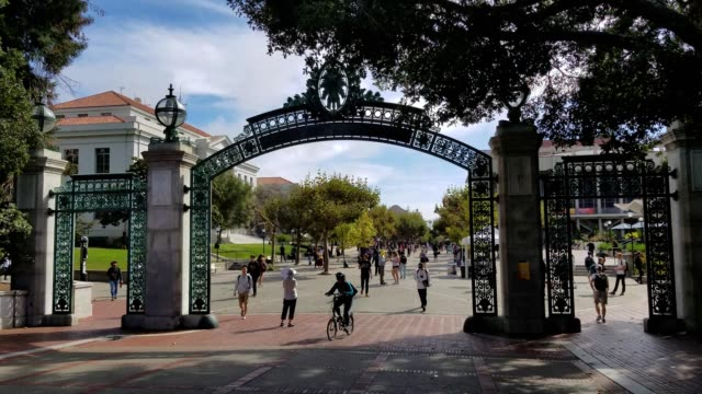 view looking south through the iconic sather gate entrance to the campus of uc berkeley in berkeley california students and pedestrians walking and... - south stock videos & royalty-free footage