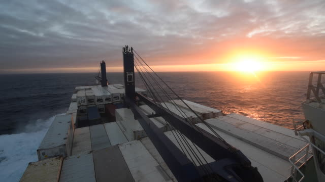 View looking toward the bow of  containers and sunset from the compass deck of a container ship crossing the Atlantic Ocean.