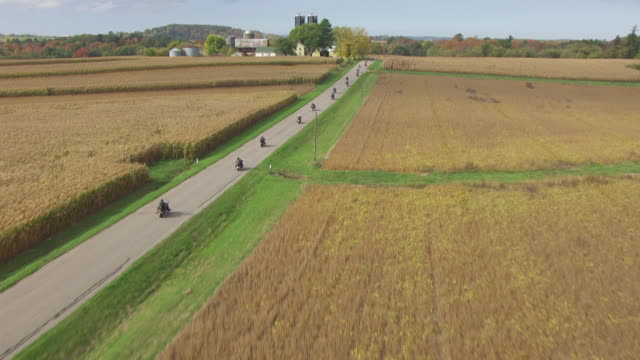 WS AERIAL TS View Low from corn field to motorcycle riders driving through curvy country road in Sauk County / Wisconsin, United States