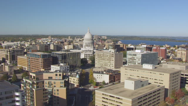 cu aerial tu view low over lake monona and directly flying over king street to state capitol towards bascom hall / madison, wisconsin, united states  - wisconsin video stock e b–roll