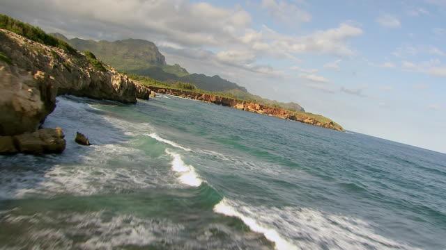 WS AERIAL View low over ocean near rock towards coastline on Island of Kauai / Hawaii, United States
