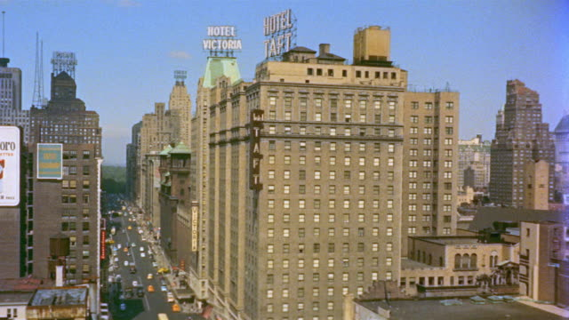stockvideo's en b-roll-footage met 1955 montage ha view north up 7th avenue of hotel taft and victoria and central park in background / traffic on 7th avenue / new york city - 1955