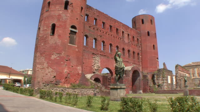 WS TD View of 1st Century Palatine Gate and Roman wall with bronze statue of Juliys Caesar / Turin, Piedmont, Italy