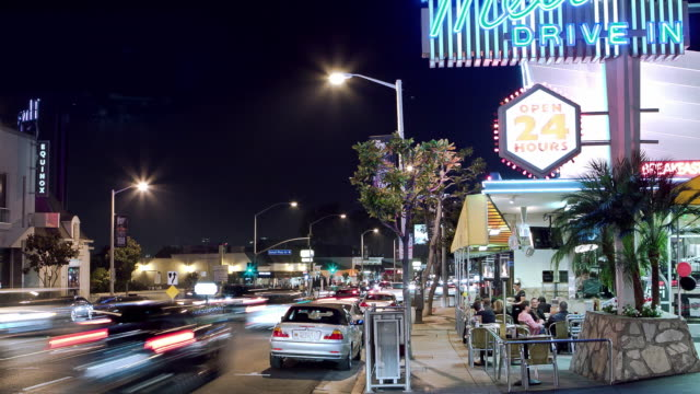 WS ZI T/L  View of 24 hour retro diner on Sunset Strip with outdoor sidewalk seating on a weekend night with view of Sunset Plaza in background / West Hollywood, California, USA