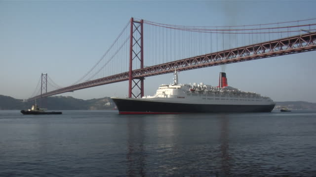 WS View of 25 de Abril bridge with Queen Elisabeth II ship moving on water / Lisbon, Portugal