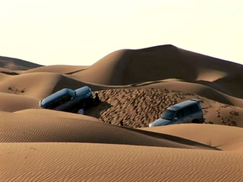 ws zo view of 4x4 vehicles parked on sand dunes in desert / muscat, oman  - trapped stock videos & royalty-free footage