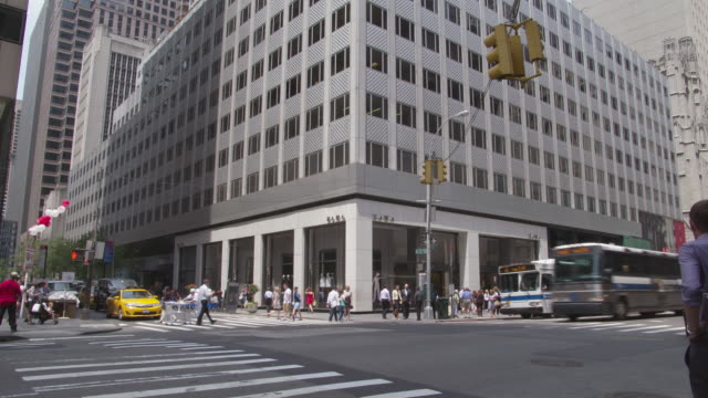 ms td view of 666 fifth avenue building to street view with cars and pedestrians / new york, united states - fifth avenue stock-videos und b-roll-filmmaterial