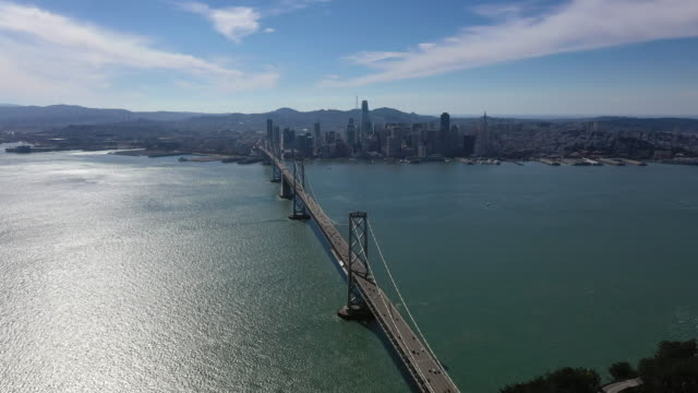 view of a big city and the bay bridge in san francisco, usa - san francisco bay bridge stock videos and b-roll footage
