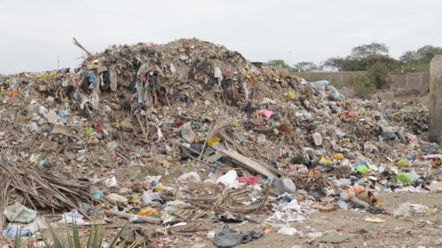 View of a big pile of trash that is on the sidewalk of a slum in Piura Peru