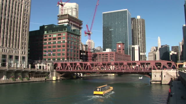 vidéos et rushes de view of a boat cruising under the bridge in chicago united states - train aérien