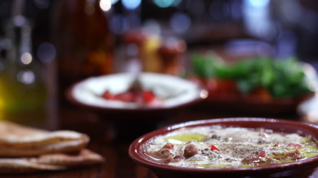 view of a bowl of ful medames on a dining table - appetiser stock videos & royalty-free footage