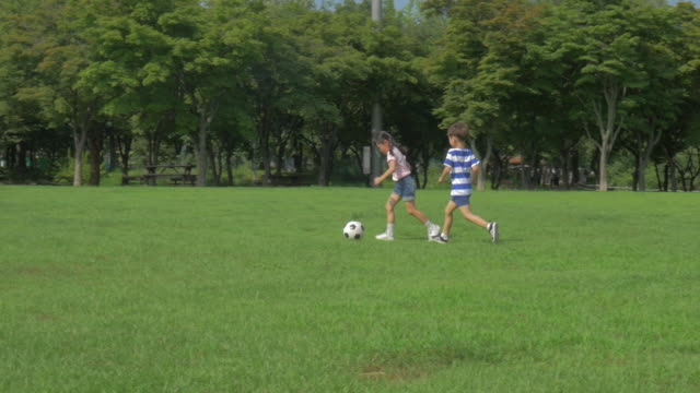 View of a boy and a girl playing soccer in summer at Seoulforest (the third largest park in Seoul city)
