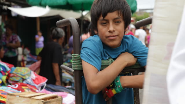 vidéos et rushes de view of a boy lending on his load carriage who is working at a street market in piura peru - péruvien