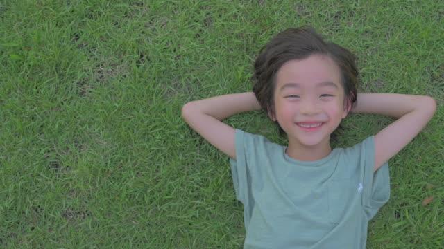 vídeos y material grabado en eventos de stock de view of a boy lying on lawn smiling in summer at seoulforest (the third largest park in seoul city) - manos detrás de la cabeza