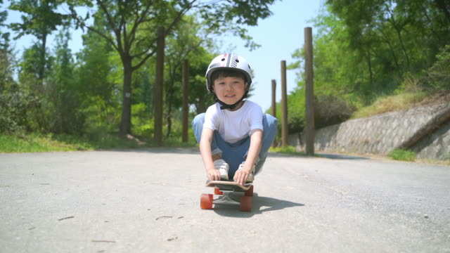 view of a boy riding a skateboard sitting on it - childhood stock videos & royalty-free footage