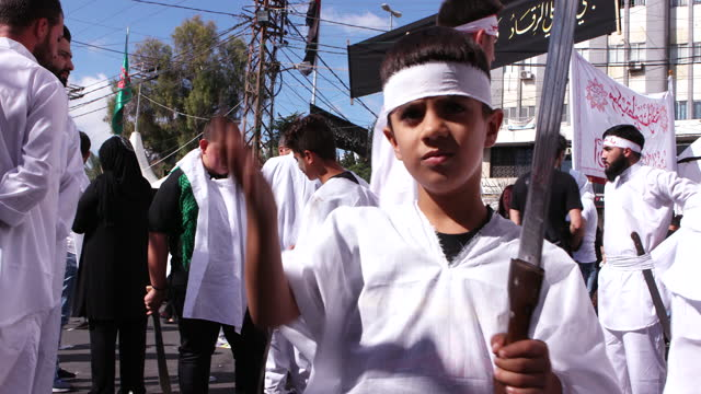 view of a boy wearing mourning white and holding a tatbir sword while hitting his head the sword is used to selfharm as part of an atonement ritual... - sword stock videos & royalty-free footage