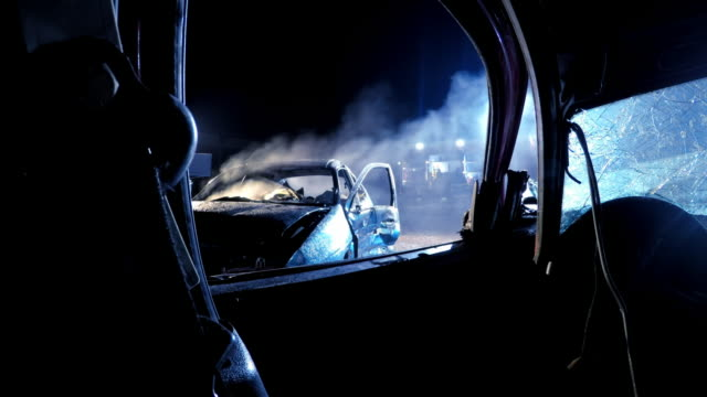 pov view of a burnt out car at night from another car - incidente automobilistico video stock e b–roll