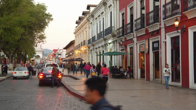 view of a busy colonial-style street at sunset, san cristobal de las casas, chiapas, mexico - mexican ethnicity stock videos & royalty-free footage