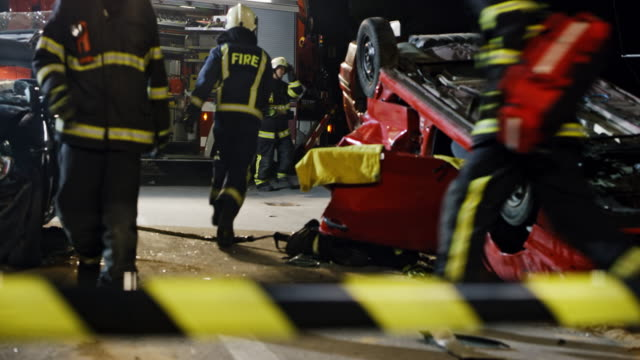 ds view of a car accident at night across the barricade tape - incidente automobilistico video stock e b–roll