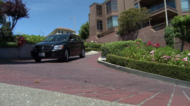 view of a car driving the sharp turns on lombard street in san francisco. - lombard street san francisco stock videos & royalty-free footage