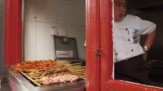A view of a chef and his shashlik in famous Wangfujing Snack Street on May 4 2017 in Beijing China Wangfujing is a main business street for tourism...