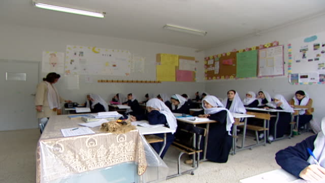 view of a classroom of druze schoolgirls in traditional school uniforms attending an english class at irfan a druze religious school in the chouf... - 女性教師点の映像素材/bロール