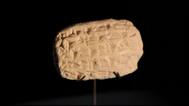 view of a clay seal impressed with ancient cuneiform writing, at the bahrain national museum. - 足根点の映像素材/bロール