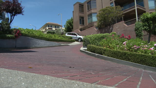 vídeos de stock, filmes e b-roll de view of a couple cars driving the sharp turns on lombard street in san francisco. - lombard street san francisco
