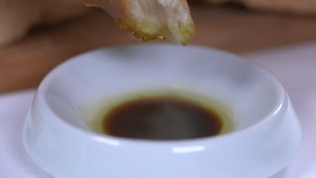 view of a crumb of bread being dipped into balsamic oil sauce - dipping stock videos & royalty-free footage