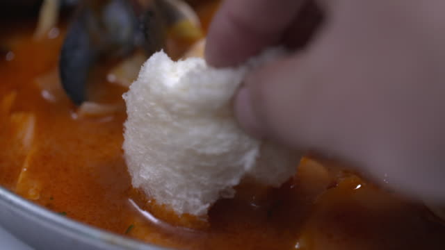 view of a crumb of bread being dipped into pecher pasta(seafood tomato stew with pasta) - dipping stock videos & royalty-free footage