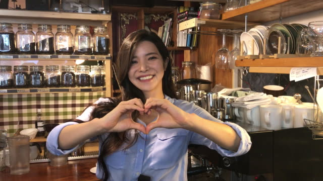 view of a female barista making heart sign with her fingers at counter in coffee shop - 韓国人点の映像素材/bロール