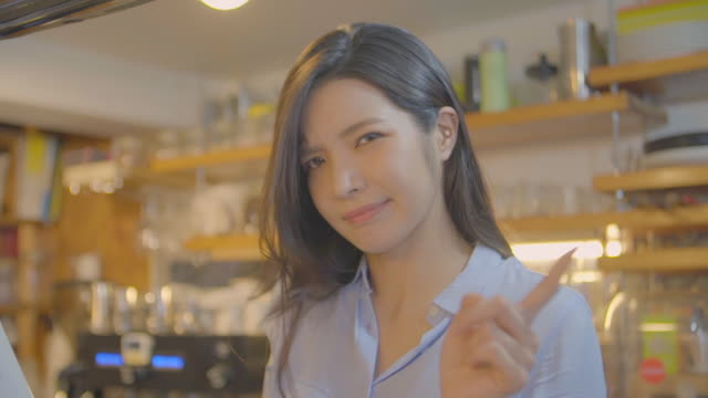 view of a female barista shaking her head and finger in coffee shop - kopf schütteln stock-videos und b-roll-filmmaterial