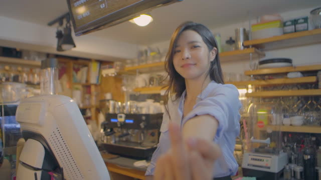 view of a female barista showing obscene gesture in coffee shop - obscene gesture stock videos and b-roll footage