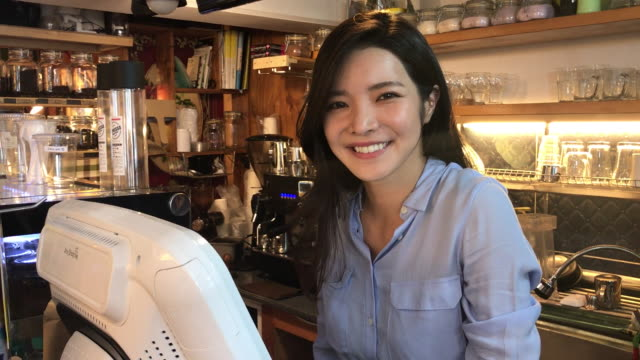 view of a female barista smiling at counter in coffee shop - 韓国人点の映像素材/bロール