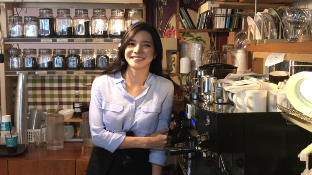 View of a female barista smiling in coffee shop