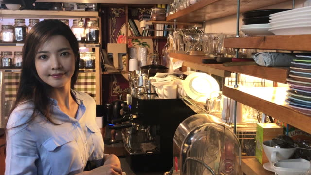 view of a female barista smiling in coffee shop - 韓国人点の映像素材/bロール