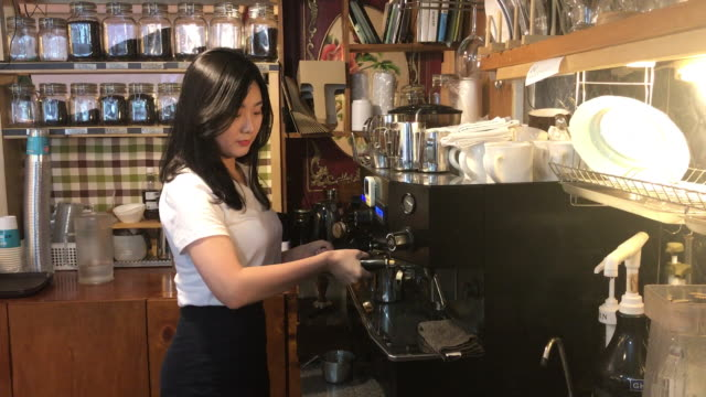 view of a female barista using coffee machine with smile - 韓国人点の映像素材/bロール