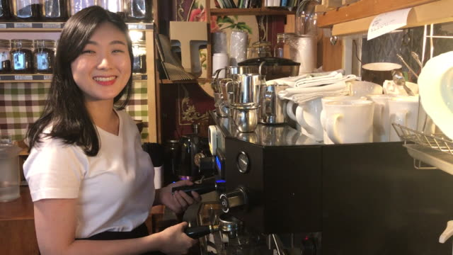 view of a female barista using coffee machine with smile - korean ethnicity stock videos & royalty-free footage