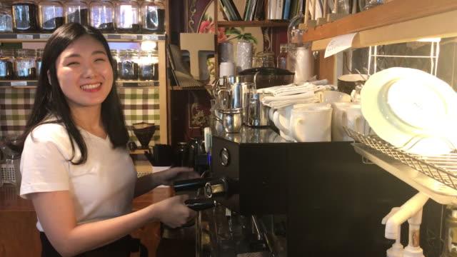 stockvideo's en b-roll-footage met view of a female barista using coffee machine with smile - middellang haar