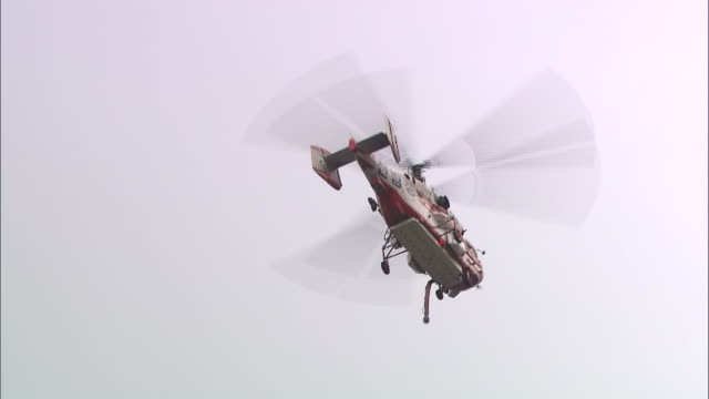 view of a fighting helicopter taking water from soyangho lake in chuncheon - propeller stock videos & royalty-free footage