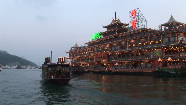 View of a floating restaurant from a moving boat at magic hour in Hong Kong China