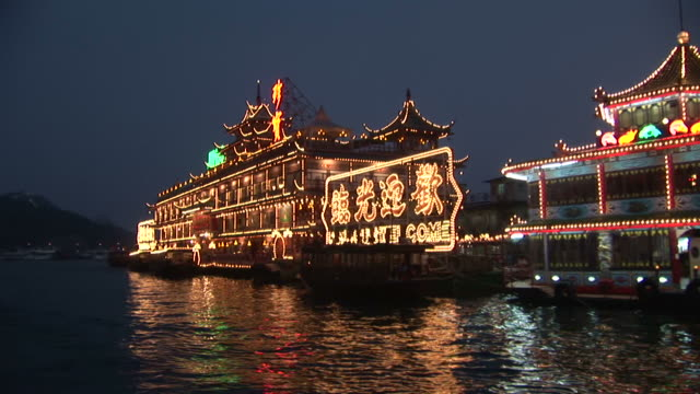 View of a floating restaurant from a moving boat at night in Hong Kong China