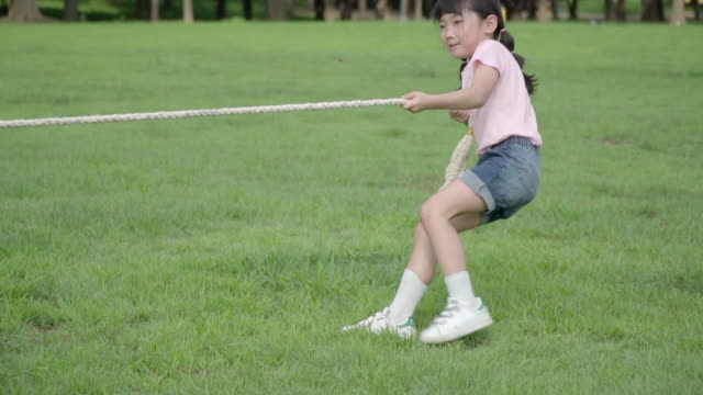 View of a girl doing tug-of-war (Game: pulling a rope) in summer at Seoulforest (the third largest park in Seoul city)