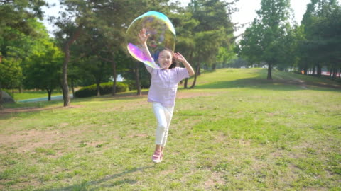 view of a girl playing with bubbles - natural parkland stock videos & royalty-free footage