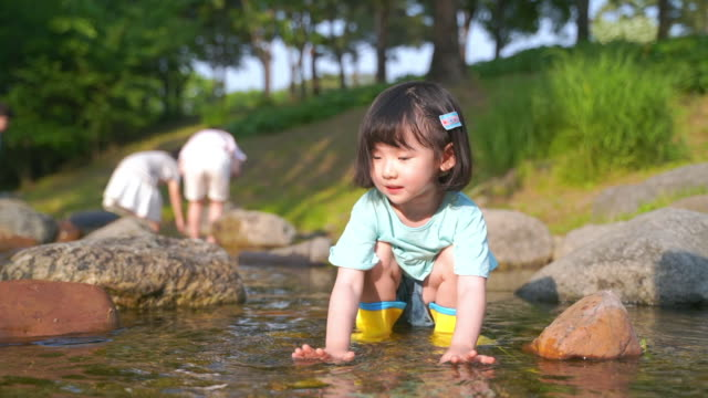 vídeos de stock, filmes e b-roll de view of a girl playing with water in the stream - riacho